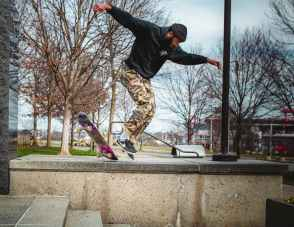 man in black jacket and brown pants jumping on skateboard